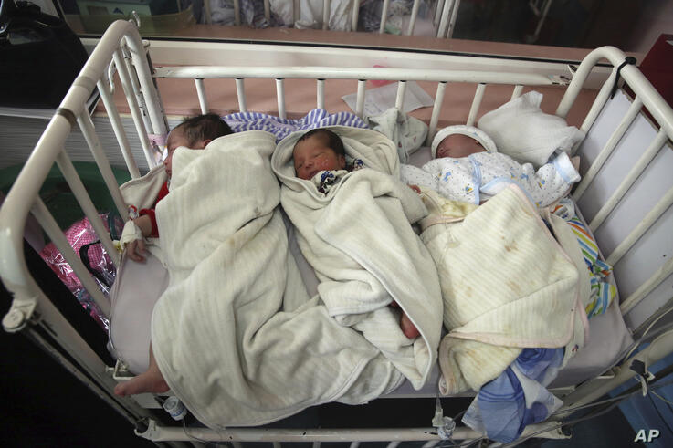 FILE - In this May 13, 2020, file photo, newborn babies lie in a bed at the Ataturk Children's Hospital a day after they were…