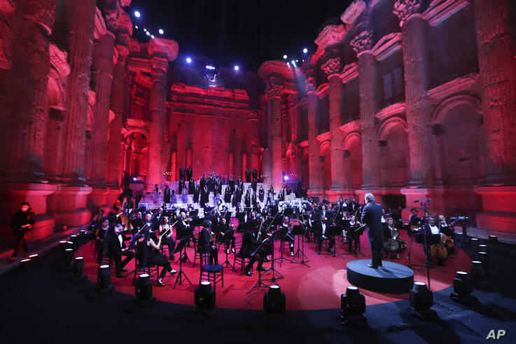 Musicians from the Lebanese Philharmonic Orchestra perform during a concert in the ancient northeastern city of Baalbek,…