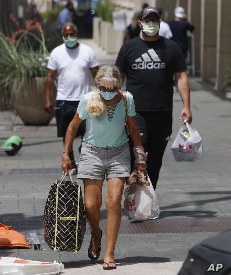 Amid concerns of the spread of COVID-19, pedestrians wear masks in downtown Dallas, Wednesday, July 8, 2020.(AP Photo/LM Otero)