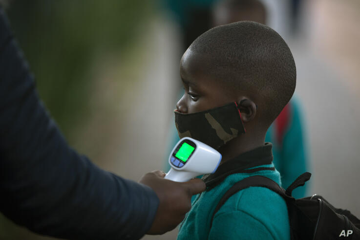 A pupil's temperature is checked on returning to school in Johannesburg, Tuesday, July 7, 2020, as more learners were permitted…