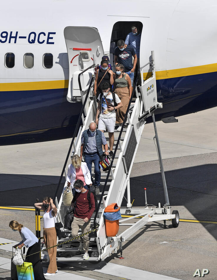 Travellers leave their plane after they arrived at the airport in Cologne, Germany, Tuesday, July 28, 2020. New test centers…