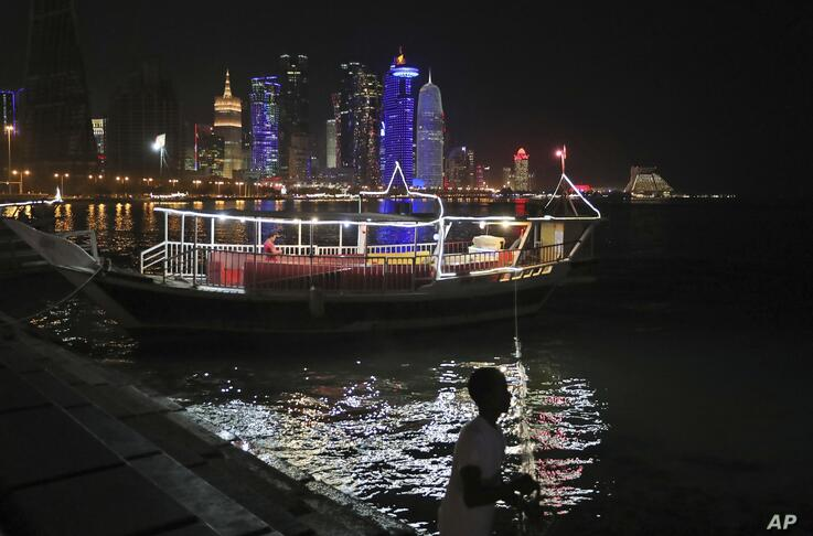 In this Wednesday, May 15, 2019 photo, a sailor tightens his dhow's rope in Doha, Qatar. (AP Photo/Kamran Jebreili)