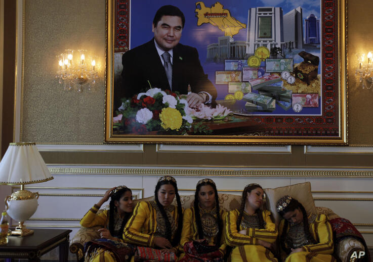 Turkmen girls dressed in traditional dresses seen seated under a portrait of Turkmenistan's President Gurbanguli…
