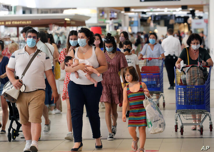 Customers wear face masks as they shop in a shopping mall in Anglet, southwestern France, Monday, July 20, 2020. Face masks are…