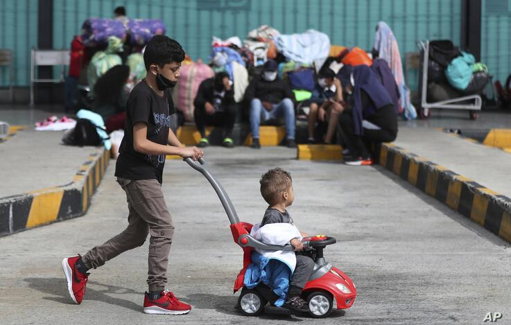A Venezuelan migrant boy pushes a toddler in a toy car as they wait for a bus to travel to the border, after breaking camp in…