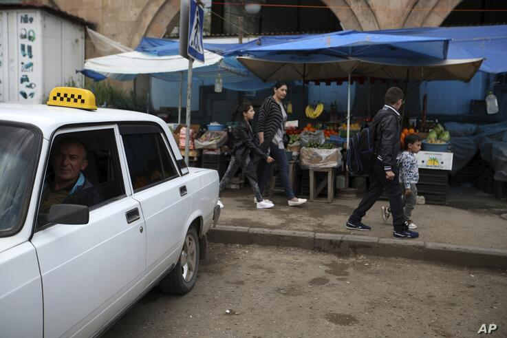 A taxi driver waits in his car at the market area of Idjevan town, northern Armenia, Sunday, May 6, 2018. (AP Photo/Thanassis…