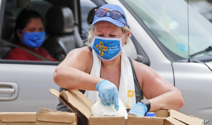 Wearing a mask amid concerns of the spread of COVID-19, volunteers Karen Cooperstein handles chilled milk for the pubic during…