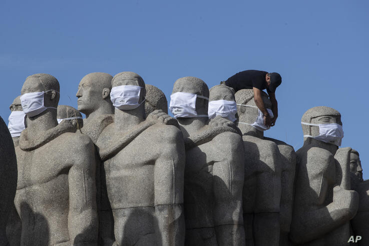 "A city worker puts face masks on the ""Monumento as Bandeiras Bandeiras,"" a monument in honor of Brazil's colonizers by Italian…"