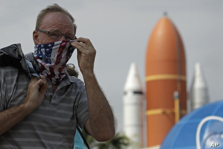 A man adjusts his mask at the Kennedy Space Center Visitor Complex, Thursday, May 28, 2020, at Cape Canaveral, Fla. The center…