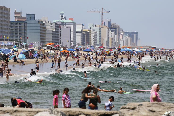 Beachgoers crowd the shoreline along the oceanfront Monday June 29, 2020, in Virginia Beach, Va. (AP Photo/Steve Helber)