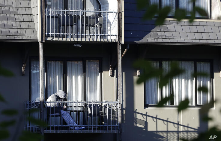 A person looks at a mobile phone on balcony at a hotel in Christchurch, New Zealand, Friday, April 10, 2020. New Zealand is…