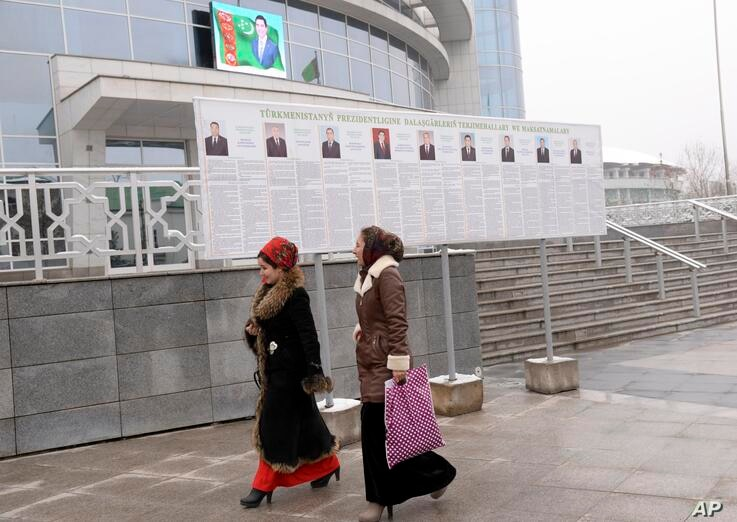 Turkmen women walk passed election posters of President Gurbanguly Berdymukhamedov, top, and other presidential candidates in…