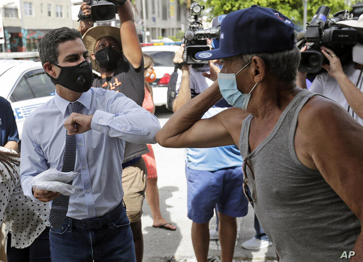 Benigno Enriquez, right, elbow-bumps Miami Mayor Francis Suarez as Suarez hands out masks to help prevent the spread of the new…