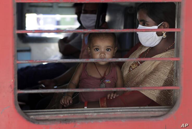 A child looks on as a special train transporting migrant workers to Bihar leaves Thane, in the western Indian state of…