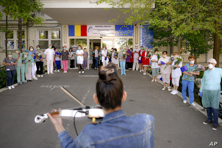 Medical staff of the Polizu maternity hospital listen to a violinist playing to entertain them and the patients in Bucharest,…