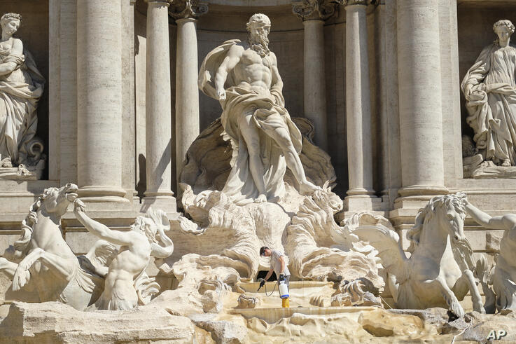 A worker cleans the Trevi fountain in Rome as part of routine maintenance Friday, June 26, 2020. (Mauro Scrobogna/LaPresse via…