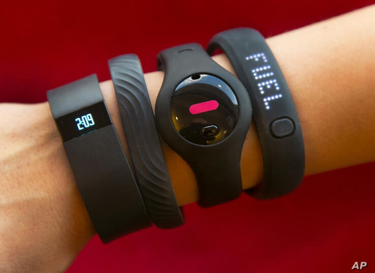 Four fitness trackers are shown in this photograph, in New York,  Monday, Dec. 16, 2013. They are, from left, Fitbit Force,…
