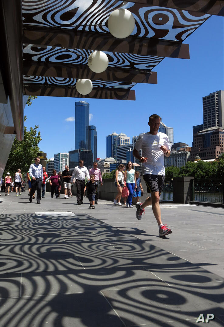 People walk and run past buildings along the waterfront of the Yarra river in Melbourne, Australia, Tuesday, Jan. 22, 2013. (AP…