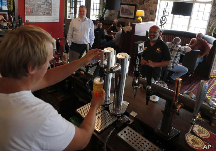 A bar man pulls a beer at the Chandos Arms pub in London, Saturday, July 4, 2020. England is embarking on perhaps its biggest…