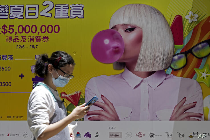 A woman wearing a face mask to help curb the spread of the coronavirus walks past a big poster in Hong Kong, Tuesday, July 28,…