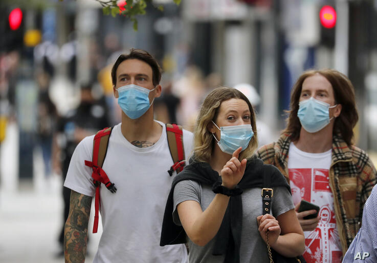 Shoppers wearing protective face masks walk along Oxford Street in London, Tuesday, July 14, 2020.Britain's government is…