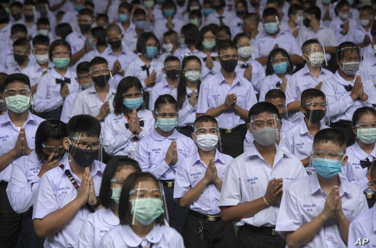 Students wearing protective gear to help curb the spread of the coronavirus pray before class at the Samkhok School in Pathum…