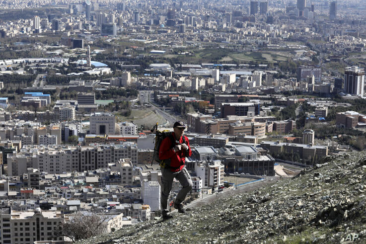 A hiker ascend a foothill of the Alborz mountain range, overlooking the capital Tehran, as he spends his New Year, or Nowruz,…