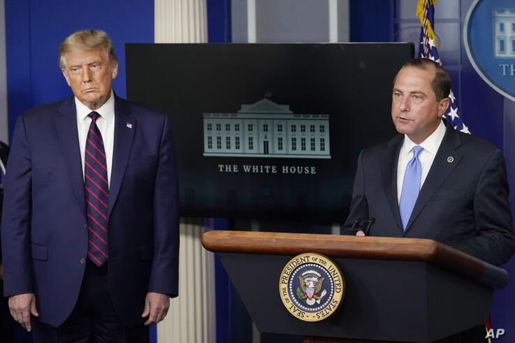 President Donald Trump listens as Health and Human Services Secretary Alex Azar speaks during a media briefing in the James…