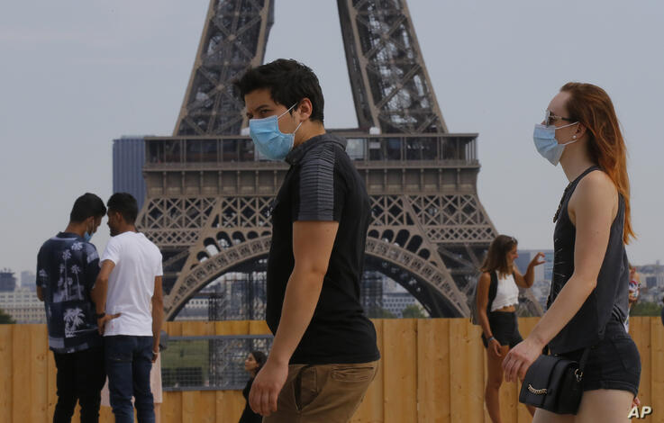 People wearing masks to prevent the spread of COVID-19 walk at Trocadero plaza near Eiffel Tower in Paris, Saturday, Aug 8,…