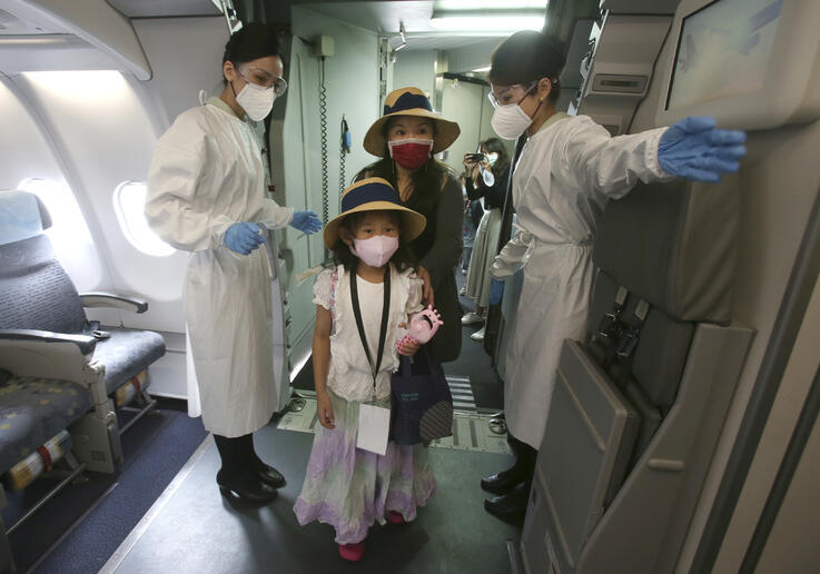 Participants are greeted by two flight attendants in protective suits and masks during a mock trip abroad at Taipei Songshan…