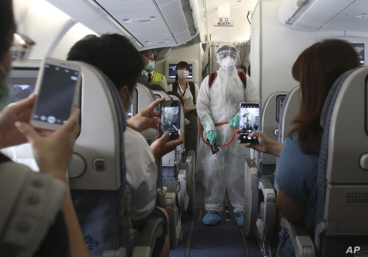 An epidemic prevention staff member shows disinfection measures to participants during a mock trip abroad at Taipei Songshan…