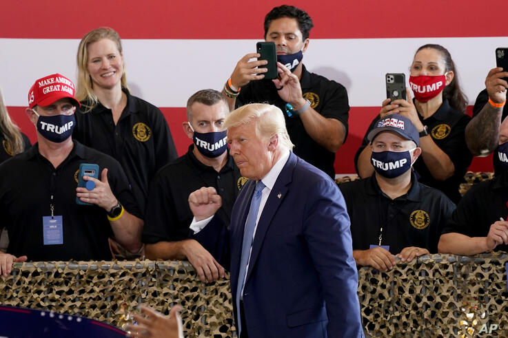 President Donald Trump pumps his fist after speaking to a crowd of supporters at the Yuma International Airport Tuesday, Aug…