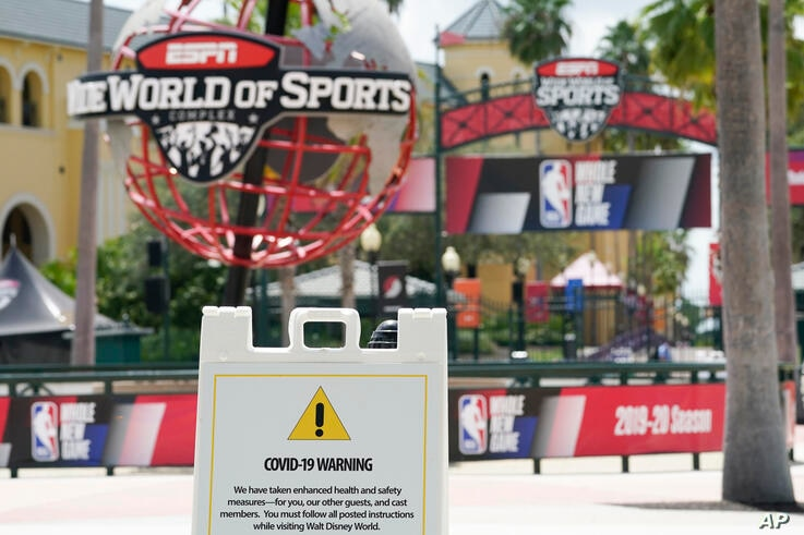 A COVID-19 warning is posted outside basketball arenas at ESPN Wide World of Sports Complex Wednesday, July 29, 2020, in…