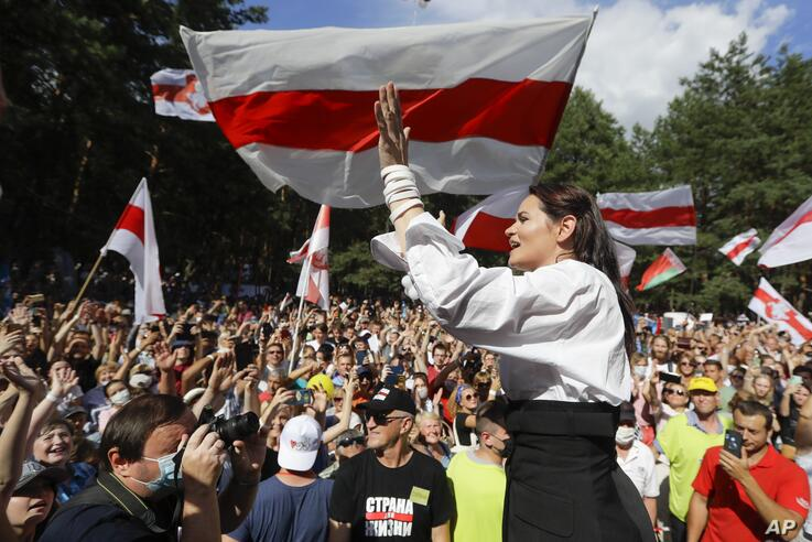 Svetlana Tikhanovskaya, candidate for the presidential elections greets people waving old Belarus flags during a meeting to…