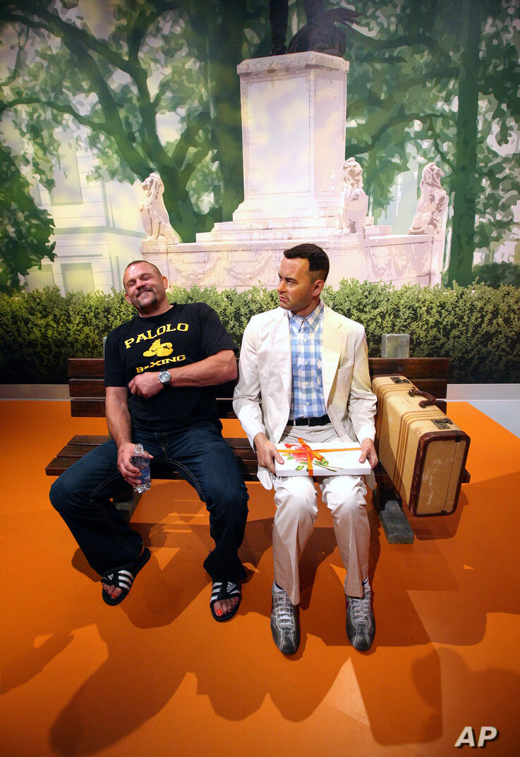 Chuck Liddell, former UFC light-heavyweight champion, left, laughs while sitting next to a wax figure of actor Tom Hanks as his…