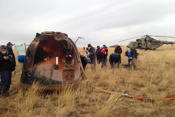 In this photo released by Roscosmos Space Agency, a Russian rescue team works near a Russian Soyuz MS-16 capsule landed near…