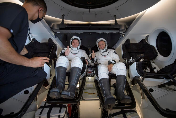 NASA astronauts Robert Behnken, left, and Douglas Hurley are seen inside the SpaceX Crew Dragon Endeavour spacecraft onboard…