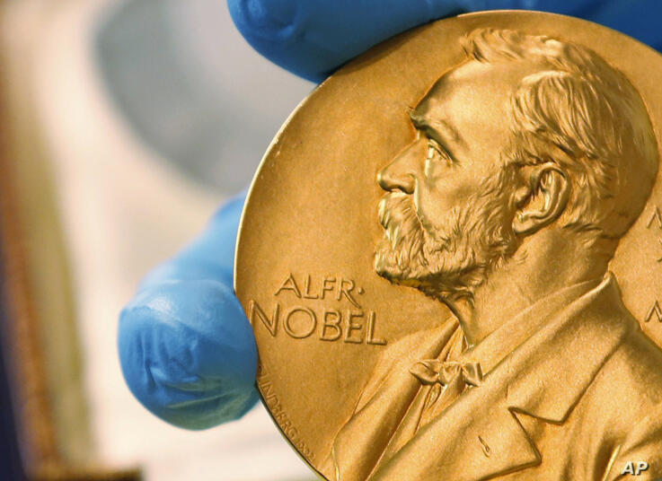 FILE - In this April 17, 2015 file photo shows a gold Nobel Prize medal. Americans Paul R. Milgrom and Robert B. Wilson have…
