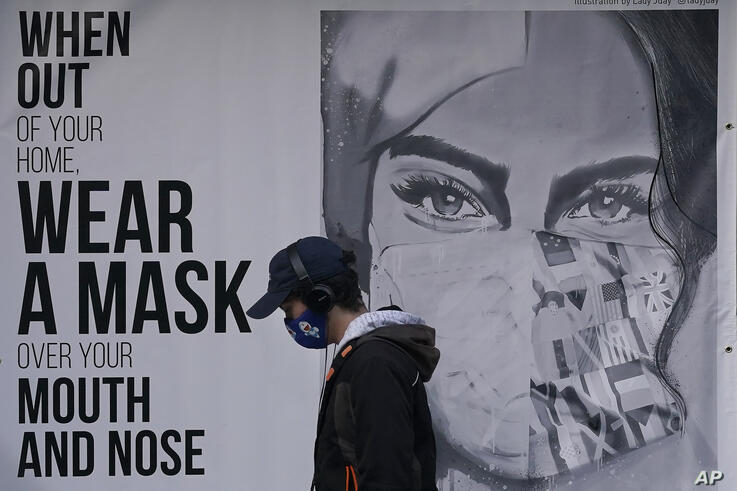 A pedestrian walks past a sign advising mask-wearing during the coronavirus outbreak in San Francisco, Saturday, Nov. ۲۱, ۲۰۲۰…