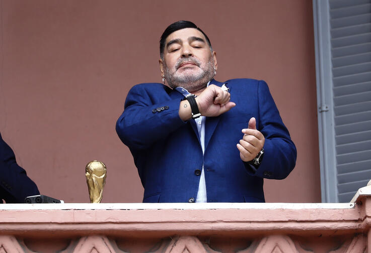 Former soccer great Diego Maradona acknowledges fans next to a small, generic replica of a FIFA World Cup soccer trophy at the…