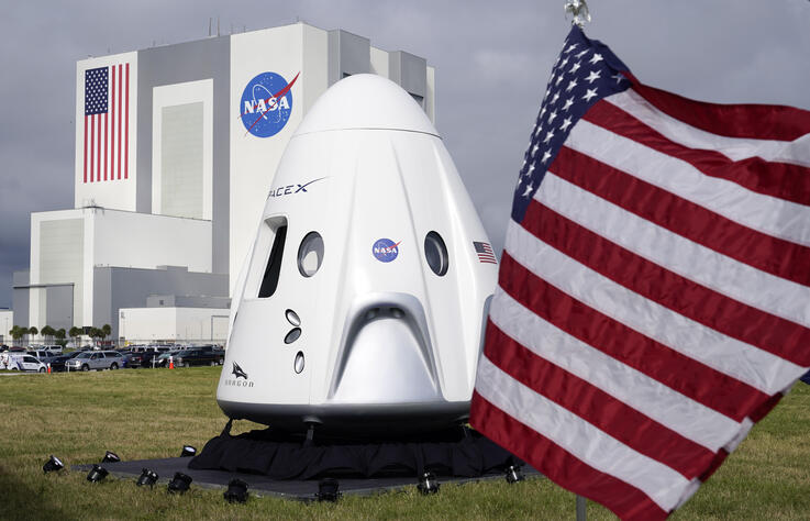 A mockup of the SpaceX crew capsule is seen on display in front of the Vehicle Assembly Building during a news conference at…