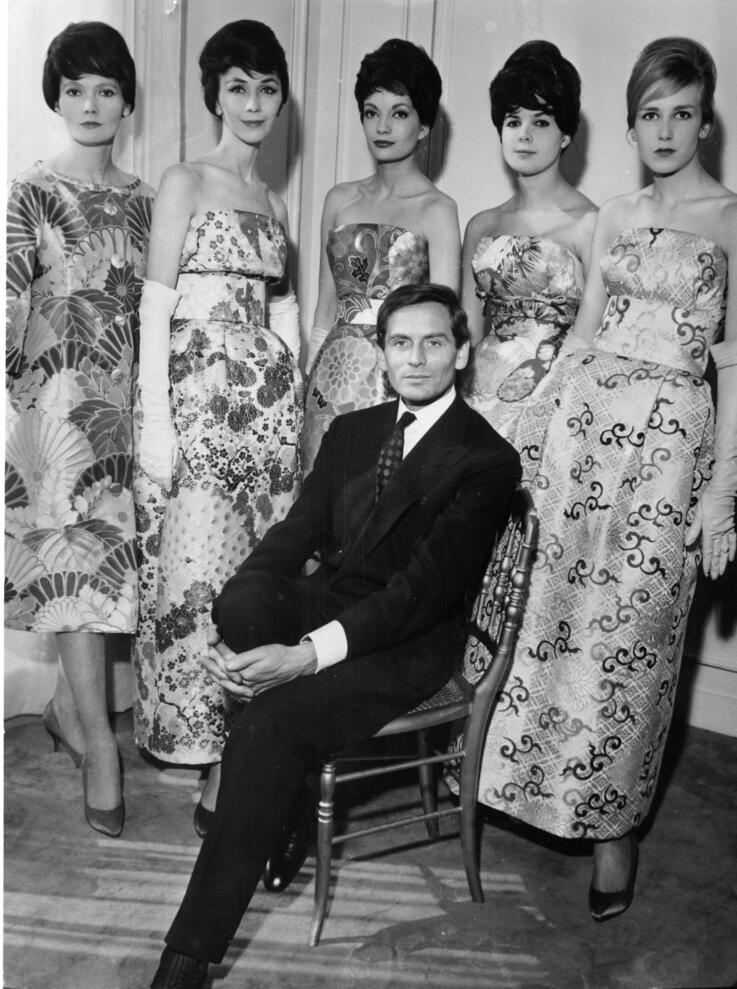 French fashion designer Pierre Cardin sits on a chair sourrounded by his models in his Paris mansion de Couture, France, March…