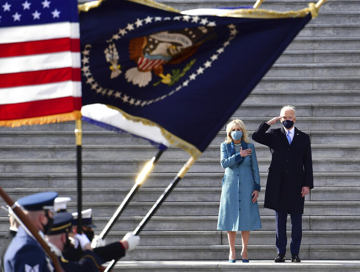 President Joe Biden salutes as his wife Jill puts her hand over her heart as they review the troops from the steps of the U.S…