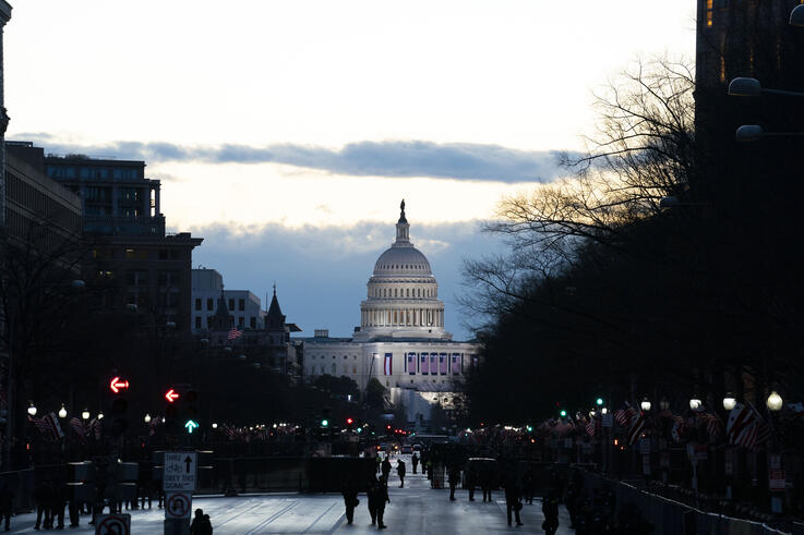 With the U.S. Capitol in the background, security members walk along the street before the 59th Presidential Inauguration at…