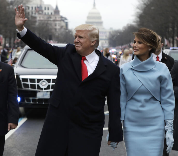 FILE- In this Jan. 20, 2017 file photo, President Donald Trump waves as he walks with first lady Melania Trump during the…