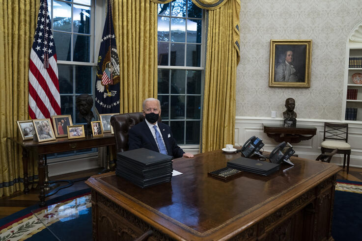 President Joe Biden signs a series of executive orders in the Oval Office of the White House, Wednesday, Jan. 20, 2021, in…