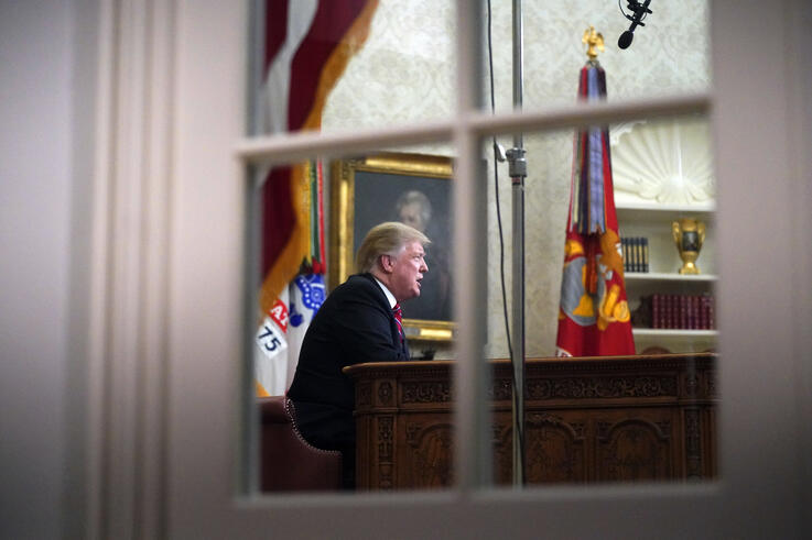 As seen from a window outside the Oval Office, President Donald Trump gives a prime-time address about border security Tuesday,…