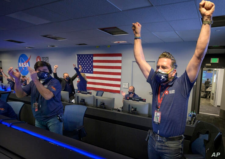 In this photo provided by NASA, members of NASA's Perseverance rover team react in mission control after receiving confirmation…