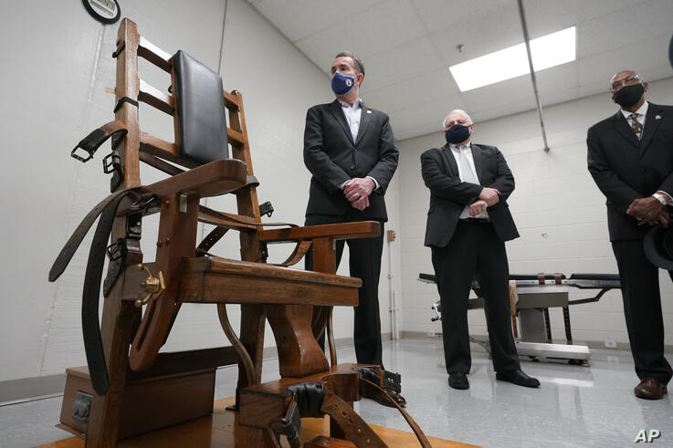 Virginia Gov. Ralph Northam, left, looks over the electric chair in the death chamber at Greensville Correctional Center with…