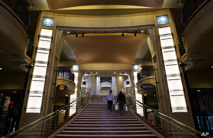Visitors walk up a staircase featuring the names of past Best Picture winners at the Academy Awards, Thursday, April 15, 2021,…